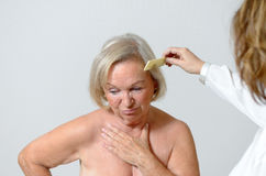 Elderly lady gets her hair combed Stock Images