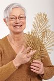 Elderly lady with golden branch fan smiling Royalty Free Stock Photo