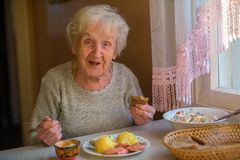 An elderly lady has dinner sitting at the table. An elderly lady has dinner sitting at the table at home stock images