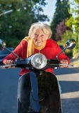 Elderly lady having fun on her scooter Royalty Free Stock Images