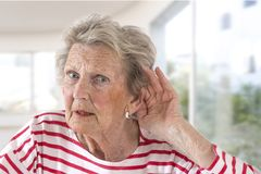 Elderly lady with hearing problems due to ageing holding her hand to her ear as she struggles to hear, profile view on. Windowns background stock images