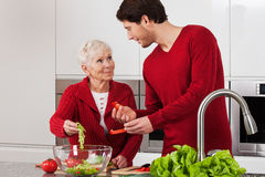 Elderly lady with her son. Making salad together Royalty Free Stock Photography