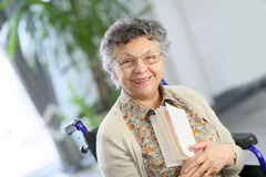 Elderly lady holding a book Royalty Free Stock Images