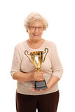 Elderly lady holding a golden trophy. Vertical shot of an elderly lady holding a golden trophy isolated on white background stock photography