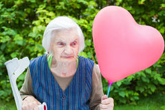 Elderly lady holding a heart shaped balloon Royalty Free Stock Photo