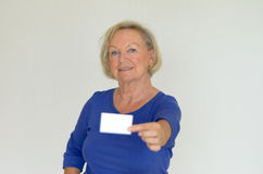 Elderly lady holding out a blank card Royalty Free Stock Images