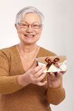 Elderly lady holding small present box smiling. Happy elderly lady holding small fancy present box Royalty Free Stock Photo