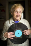 Elderly lady is holding a vinyl record. Active aging. With place for your text on disk. Royalty Free Stock Photos