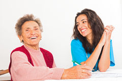 Elderly Lady with Homecare Nurse. Happy elderly women with kind social services provider nurse laughing Royalty Free Stock Images
