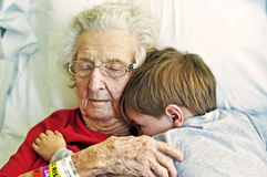 Elderly lady in hospital hugs young grandson royalty free stock photography