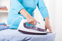 Elderly lady during ironing. Shirt at home stock photography
