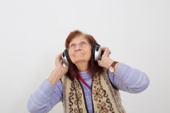 Elderly lady listening music with headphones Royalty Free Stock Photo