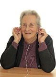 Elderly lady listening to music, white background Royalty Free Stock Photo
