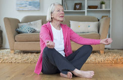 Elderly lady meditating at home Royalty Free Stock Images