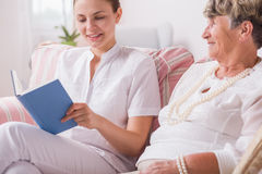 Elderly lady and nurse reading Royalty Free Stock Photography