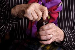 Elderly lady opening a medicine bottle Stock Photo