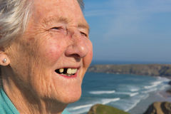 Elderly lady pensioner with dental problems and a tooth missing. By beautiful coastal scene Royalty Free Stock Image