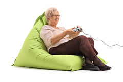 Elderly lady playing video games. Seated on a comfortable green beanbag isolated on white background Stock Photos