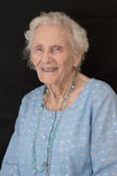 Elderly lady portrait. Happy and smiling elderly lady with black background Royalty Free Stock Photography