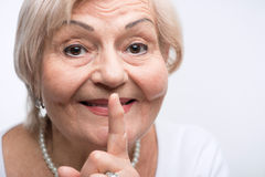 Elderly lady putting finger on her mouth Royalty Free Stock Photos