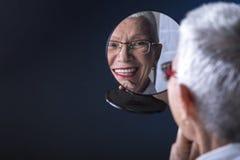 Elderly lady putting make up on stock photography