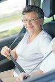 Elderly lady putting on seatbelt Stock Photo