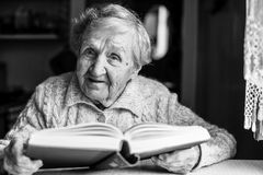 Elderly lady reading a book, sits at the table. Royalty Free Stock Image