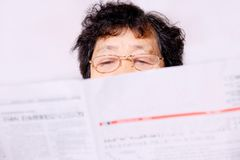 Elderly lady reading newspaper. A picture of a elderly chinese lady reading newspaper Royalty Free Stock Images