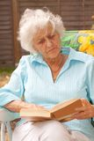 Elderly Lady Reading Outdoors Royalty Free Stock Images