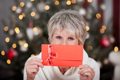 Elderly lady with a red gift voucher. Elderly lady with a red gift Christmas voucher in front of a tree with a sparkling bokeh of lights Royalty Free Stock Images