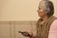 Elderly lady with remote control Royalty Free Stock Images