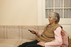 Elderly lady with remote control Royalty Free Stock Photos