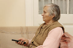 Elderly lady with remote control Royalty Free Stock Photography