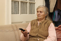 Elderly lady with remote control stock photography