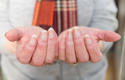 Elderly lady`s hands in gesture of need. Close up of elderly lady`s hands held out in front of her in a gesture of need Royalty Free Stock Image