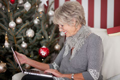 Elderly lady sending Christmas greetings Royalty Free Stock Images