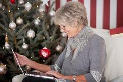 Elderly lady sending Christmas greetings Royalty Free Stock Images
