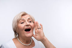 Elderly lady shouting putting hands by her mouth Royalty Free Stock Photo