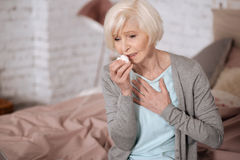 Elderly lady sick woman feeling bad. Feeling discomfort. Pretty aged woman sitting on bed and touching her chest while coughing Royalty Free Stock Photos