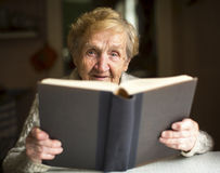 Elderly lady sits and reads big book at the table in house. Royalty Free Stock Photography