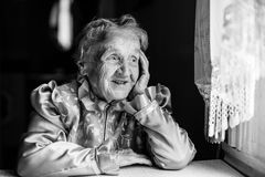 Elderly lady sits at the table and looking out the window. Royalty Free Stock Images
