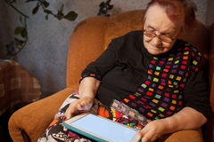 Elderly lady sitting in an chair using a tablet Stock Images