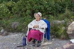 Elderly lady sitting in a chair. Elderly lady wearing a hat and smiling sitting in a chair Royalty Free Stock Image