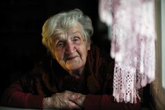 Elderly lady sitting in the dark in the house. Portrait of an elderly lady sitting in the dark in the house stock photography