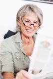 Elderly lady sitting reading the news Royalty Free Stock Image