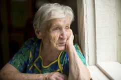An elderly lady skeptically looking out the window. Sorrow. Royalty Free Stock Images