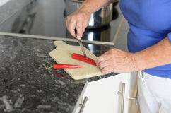 Elderly lady slicing red chili peppers Royalty Free Stock Image