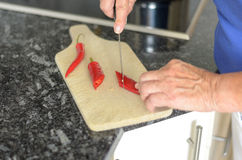 Elderly lady slicing red chili peppers Stock Photography