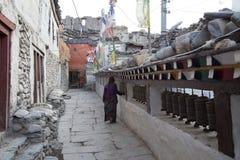 Elderly lady spinning prayer wheels Stock Photography