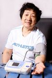 Elderly lady taking blood pressure. A picture of a chinese elderly lady taking blood pressure Royalty Free Stock Photos